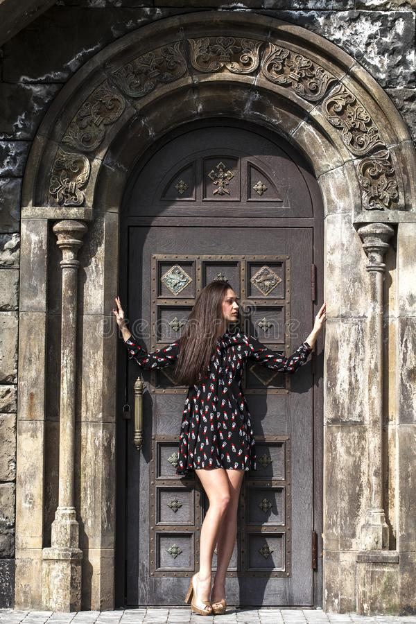 Portrait young beautiful brunette woman in dress posing against the backdrop of an old castle in the Gothic style. Full body portrait young beautiful brunette royalty free stock images