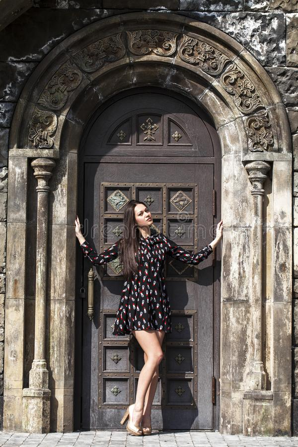 Portrait young beautiful brunette woman in dress posing against the backdrop of an old castle in the Gothic style. Full body portrait young beautiful brunette stock image