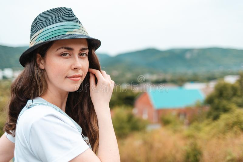 Portrait of a young beautiful brunette woman in hat posing against a rural view stock image
