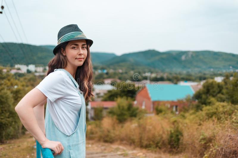 Portrait of a young beautiful brunette woman in hat posing near the railing against a rural view royalty free stock photography
