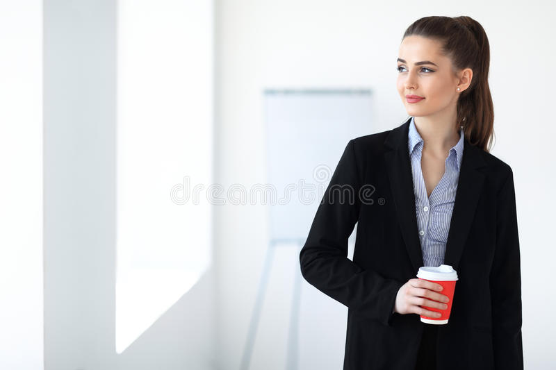 Portrait of young beautiful business woman with cup of coffee in. The office background stock photos