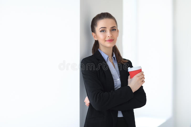 Portrait of young beautiful business woman with cup of coffee in. The office background royalty free stock images