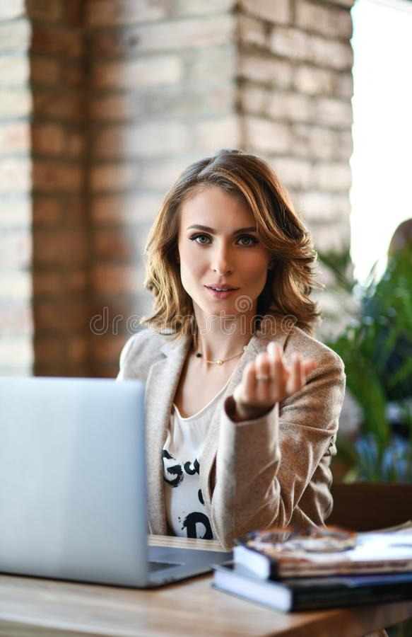 Young beautiful business woman work on portable laptop computer, charming female student using net-book while sitting in cafe bar stock photography