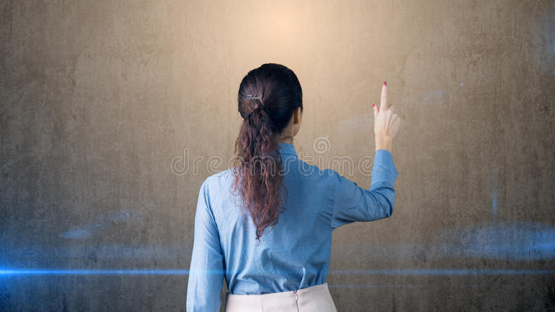 Portrait of young beautiful business woman writing on an invisible board stock photography