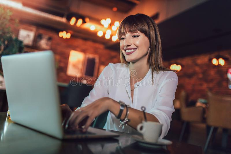 Young beautiful businesswoman enjoying coffee during work on portable laptop computer. Portrait of a young beautiful businesswoman enjoying coffee during work on royalty free stock photos