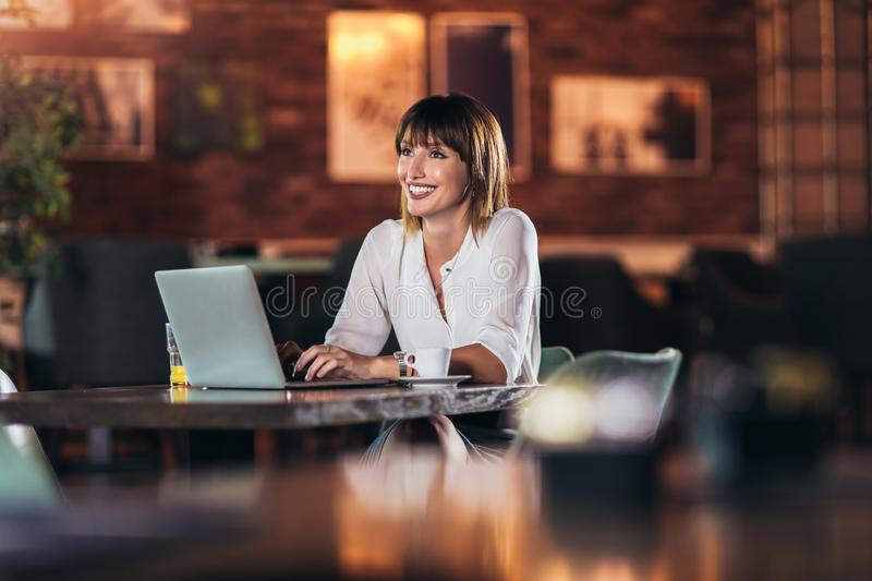 Young beautiful businesswoman enjoying coffee during work on portable laptop computer. Portrait of a young beautiful businesswoman enjoying coffee during work on stock images