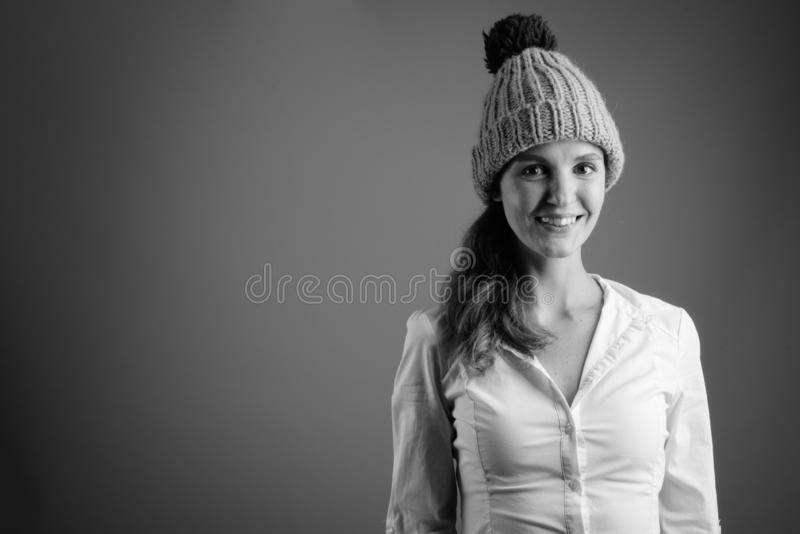 Portrait of young beautiful businesswoman wearing winter beanie hat royalty free stock photography