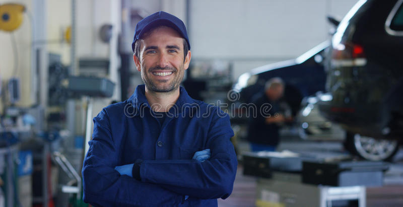 Portrait of a young beautiful car mechanic in a car workshop, in the background of service. Concept: repair of machines, fault dia royalty free stock photo