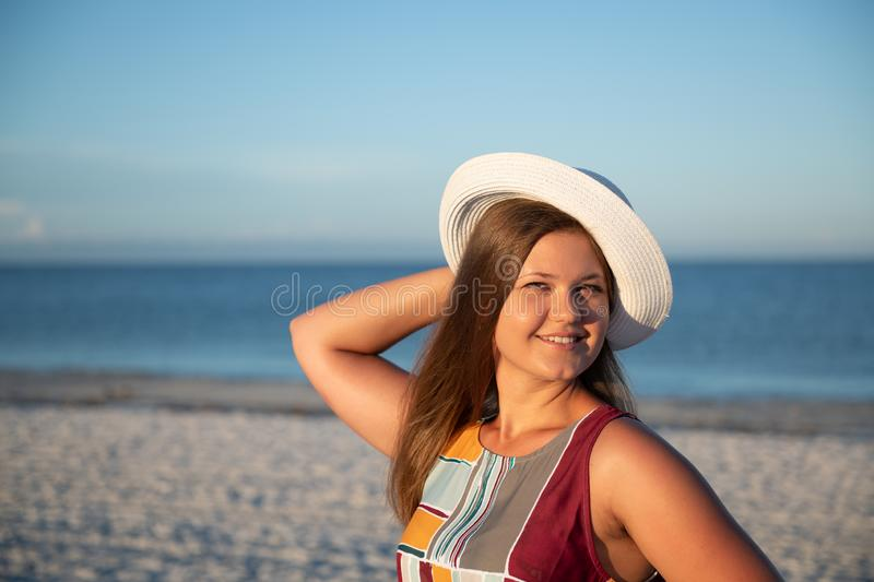 Young woman on the beach. Portrait of a young  beautiful carefree woman walking on sunny beach wearing dress and hat royalty free stock photos