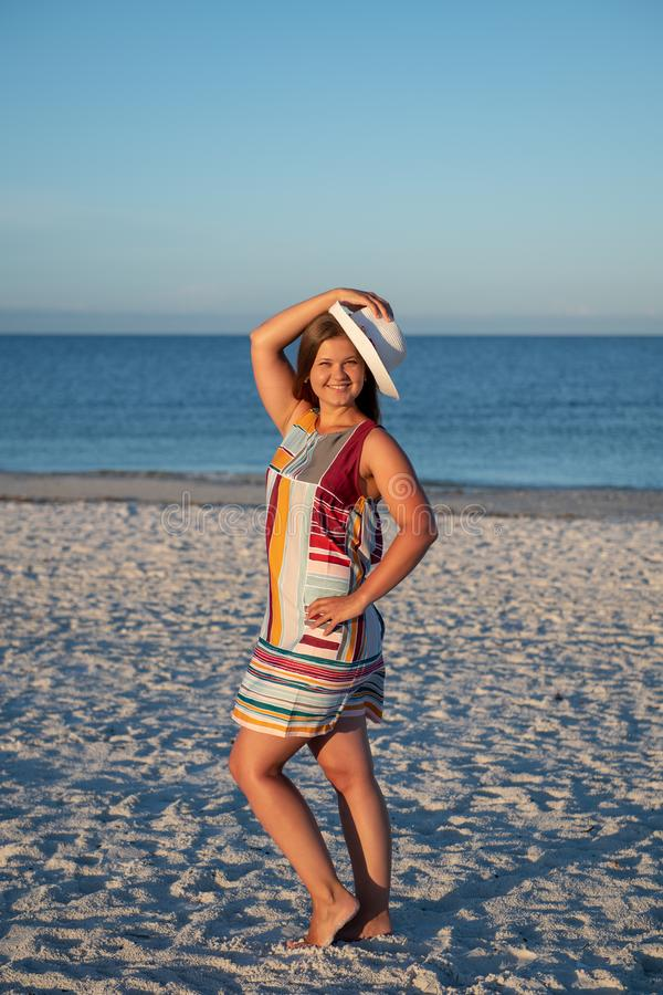 Young woman on the beach. Portrait of a young  beautiful carefree woman walking on sunny beach wearing dress and hat royalty free stock photography