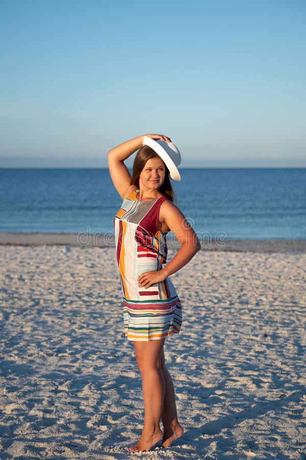 Young woman on the beach. Portrait of a young  beautiful carefree woman walking on sunny beach wearing dress and hat stock images