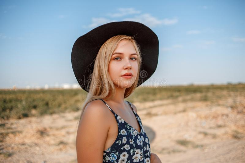 Portrait of a young beautiful caucasian blonde girl in a blue dress with a floral print and a black hat standing on a sandy royalty free stock images