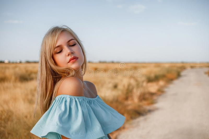 Portrait of a young beautiful caucasian blonde girl in a light blue dress standing on a field with sun-dried grass next to a small royalty free stock photography