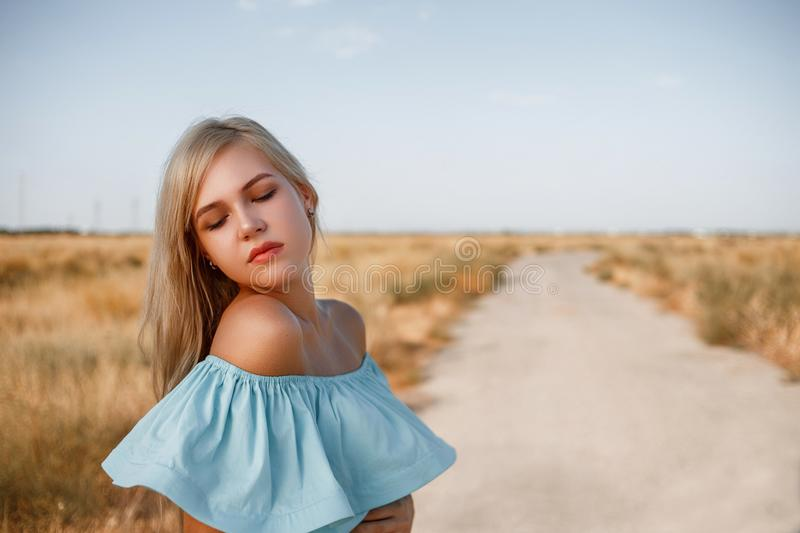 Portrait of a young beautiful caucasian blonde girl in a light blue dress standing on a field with sun-dried grass next to a small. Country road royalty free stock image