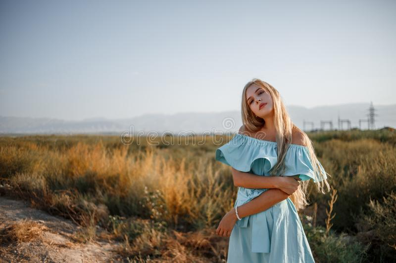 Portrait of a young beautiful caucasian blonde girl in a light blue dress standing on a field with sun-dried grass next to a small. Country road stock images