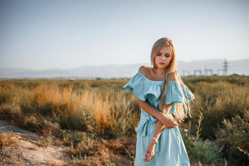 Portrait of a young beautiful caucasian blonde girl in a light blue dress standing on a field with sun-dried grass next to a small. Country road stock photos