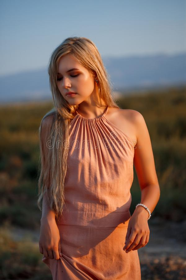 Portrait of a young beautiful Caucasian blonde woman in a pink dress in a deserted field against the sunset stock photography