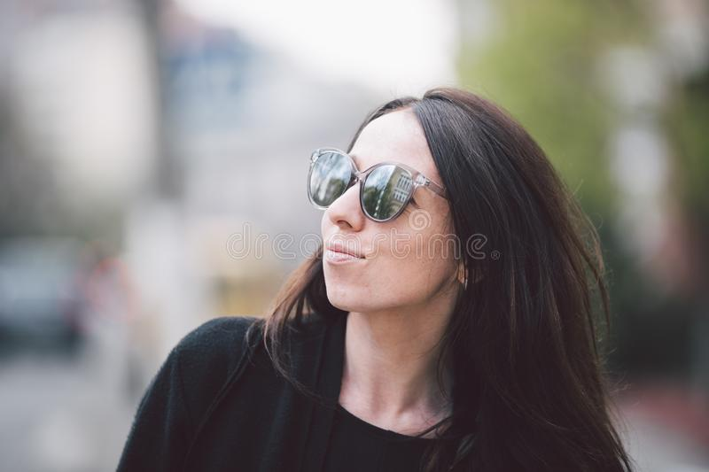 Portrait of a young beautiful caucasian woman on the background of the street. Model girl with long hair and sunglasses stock photo