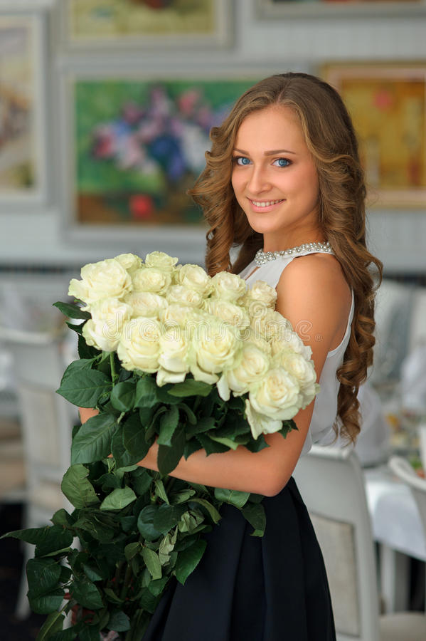 Portrait of a young beautiful caucasian woman with bouquet of white roses. Smiling Girl looking at camera stock photography