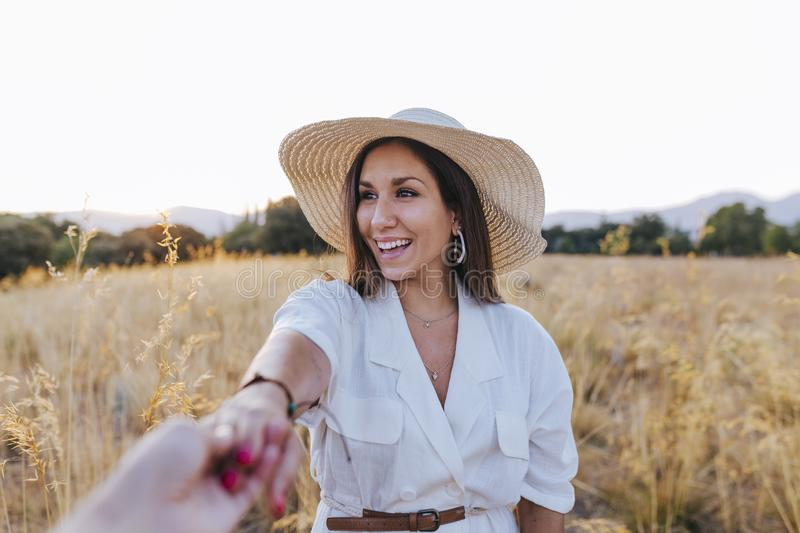 Portrait of young beautiful caucasian woman outdoors at sunset in a yellow field. wearing a modern hat and smiling. Holding hands stock photo