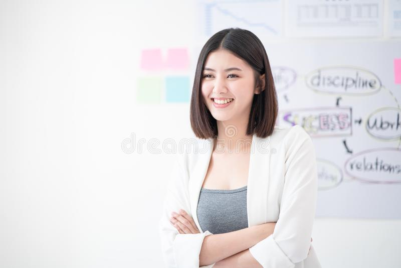 Portrait of young beautiful and confident business woman smiling and standing in front of meeting board or planning chart give the stock photo