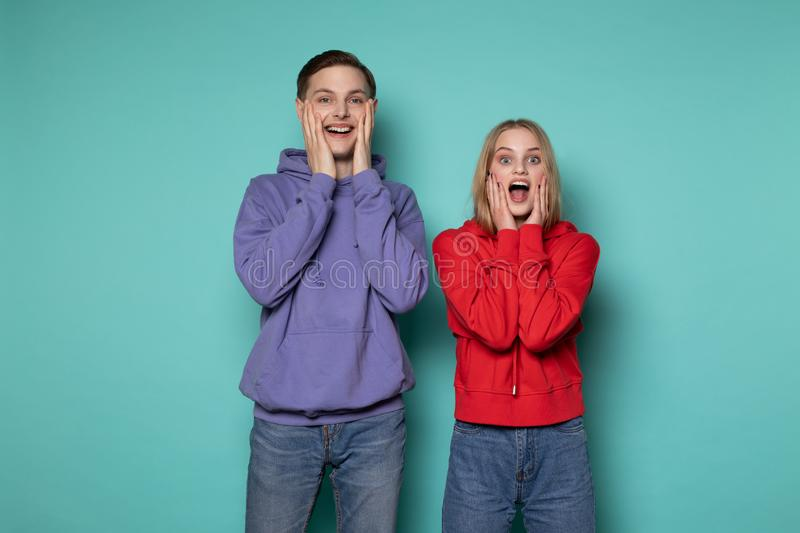 Portrait of young beautiful couple in casual clothes screaming in surprise or delight and touching cheeks stock image