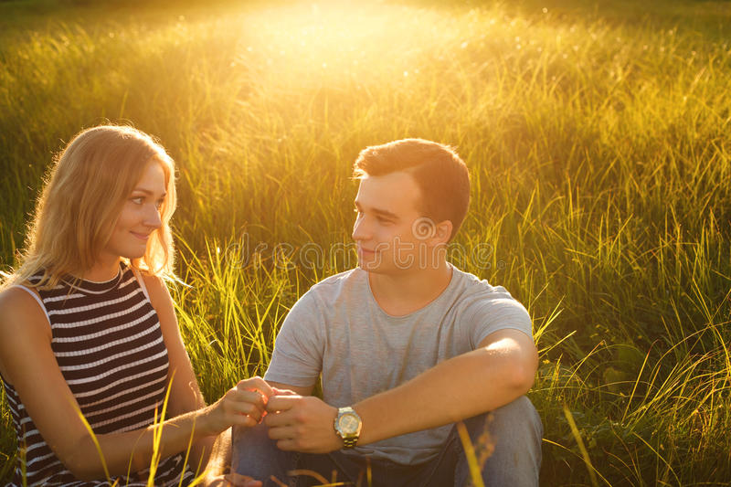 A portrait of young beautiful couple sitting on grass field holding hands looking at each other with great love enjoing nice summe stock image