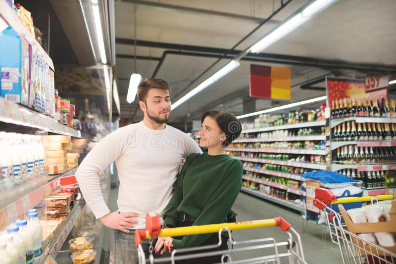 Portrait of a young beautiful couple in the store. Loving couple looking at each other in a supermarket stock photography