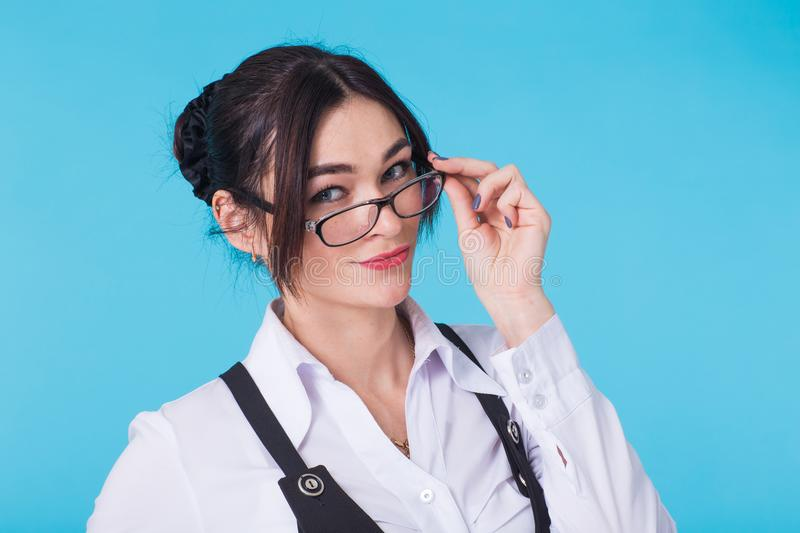 Portrait of young beautiful cute cheerful student girl with glasses smiling looking at camera over blue background. royalty free stock photo