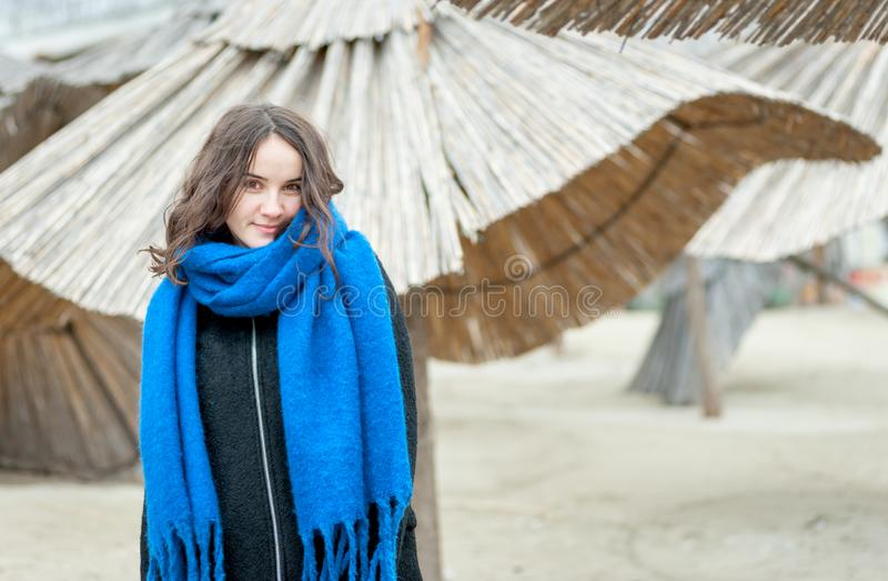 Portrait of young beautiful and cute girl in black coat and blue scarf outdoors on the cold weather with reed sunshades in the bac stock photography