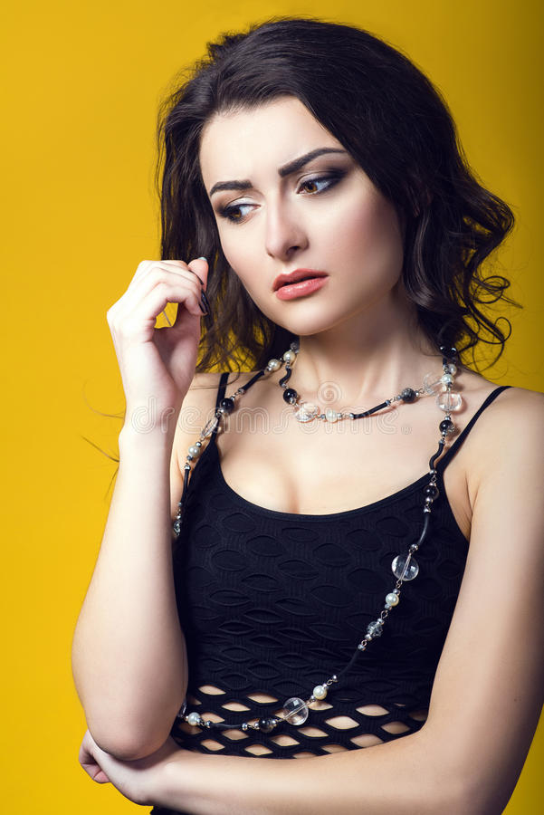 Portrait of a young beautiful dark haired concerned woman wearing black net top and glass beads looking worried and upset royalty free stock photos