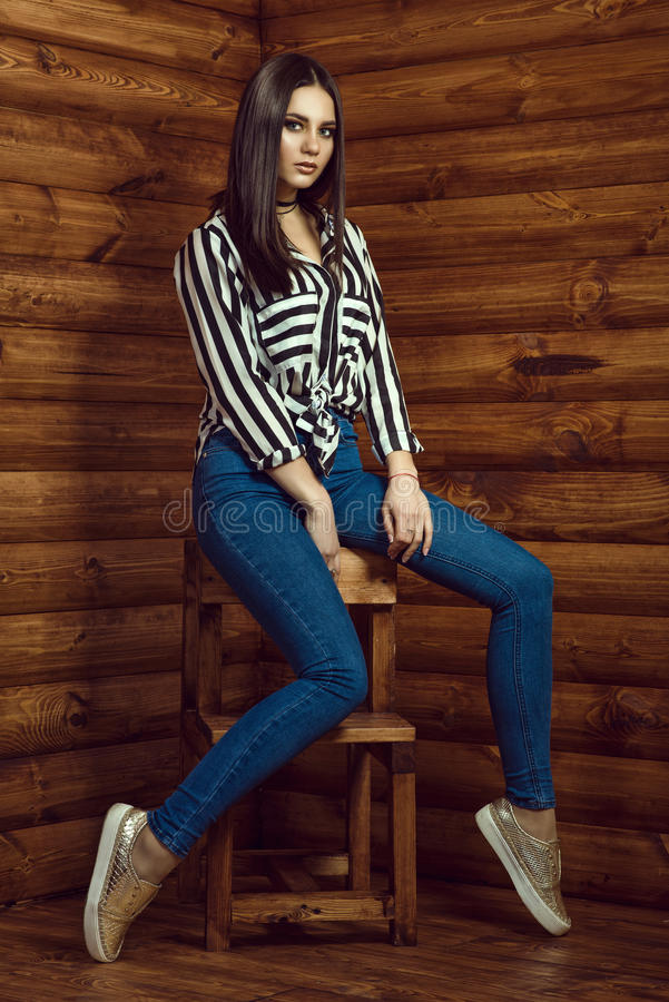 Portrait of young beautiful dark-haired model wearing skinny high-waisted jeans, striped shirt, choker and golden sneakers royalty free stock photos