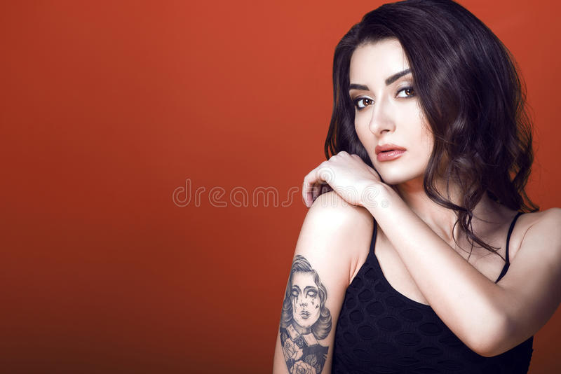 Portrait of a young beautiful dark haired tattooed woman wearing black net top, holding her hand on the shoulder with guarded look royalty free stock images