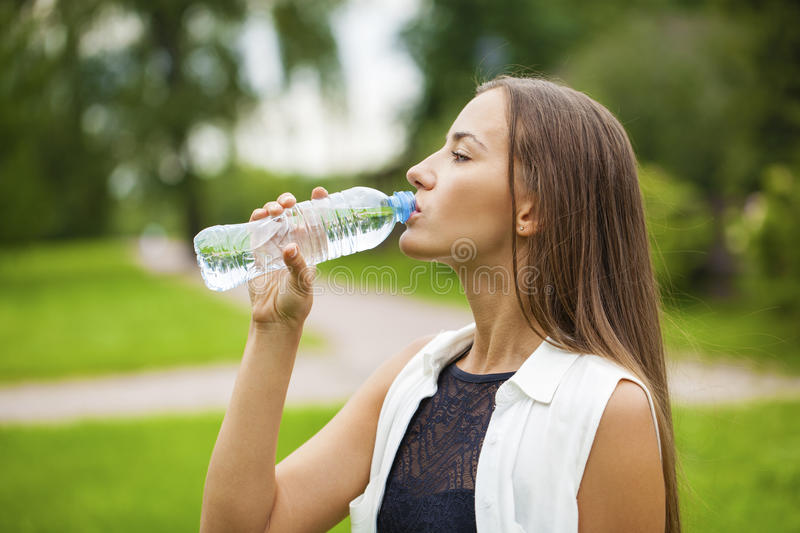 Portrait of young beautiful dark haired woman drinking water stock photography
