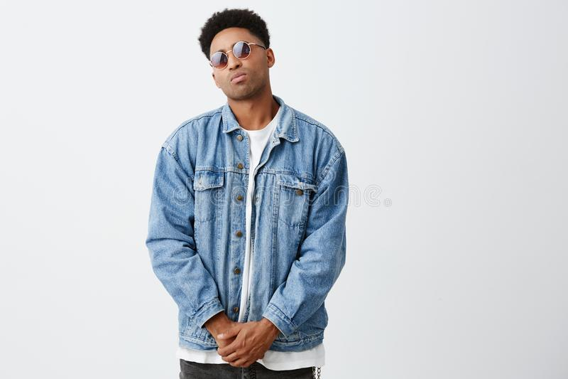 Portrait of young beautiful dark-skinned man with afro hairstyle in casual fashionable clothes and tan glasses holding stock photos