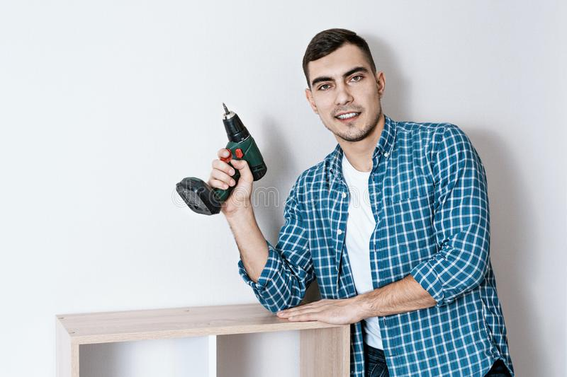 Portrait of a young beautiful European man with an electric screwdriver in his hand, a collector of furniture. copy space royalty free stock photography