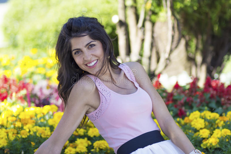 Portrait of young beautiful fashion woman on a flowers background. Portrait of young brunette beautiful fashion woman in a blooming garden royalty free stock photo