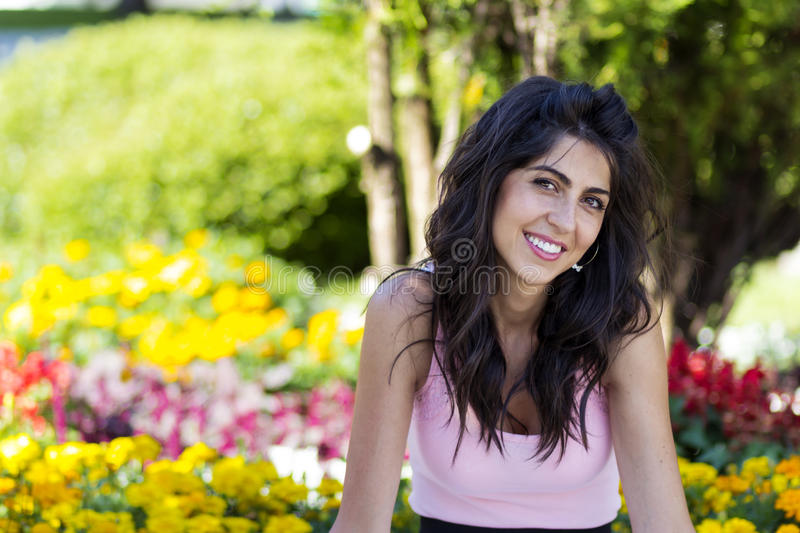 Portrait of young beautiful fashion woman on a flowers background. Portrait of young brunette beautiful fashion woman in a blooming garden royalty free stock image