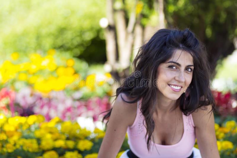 Portrait of young beautiful fashion woman on a flowers background. Portrait of young brunette beautiful fashion woman in a blooming garden royalty free stock photography