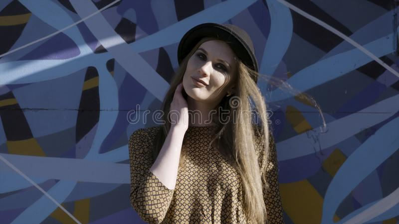 Portrait of young beautiful fashionable woman with black hat posing on blue graffity background. Action. Model wearing royalty free stock photo