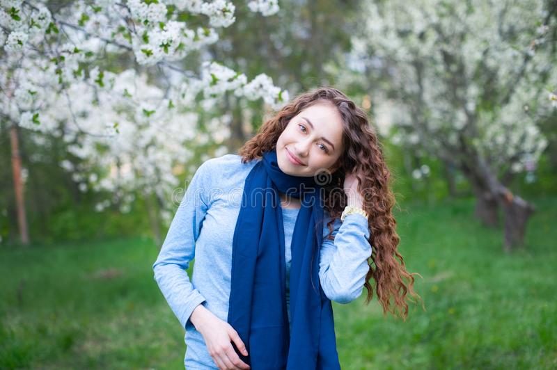 Portrait of a young beautiful fashionable woman in spring blossoming park. Happy girl posing in a blooming garden with white stock image