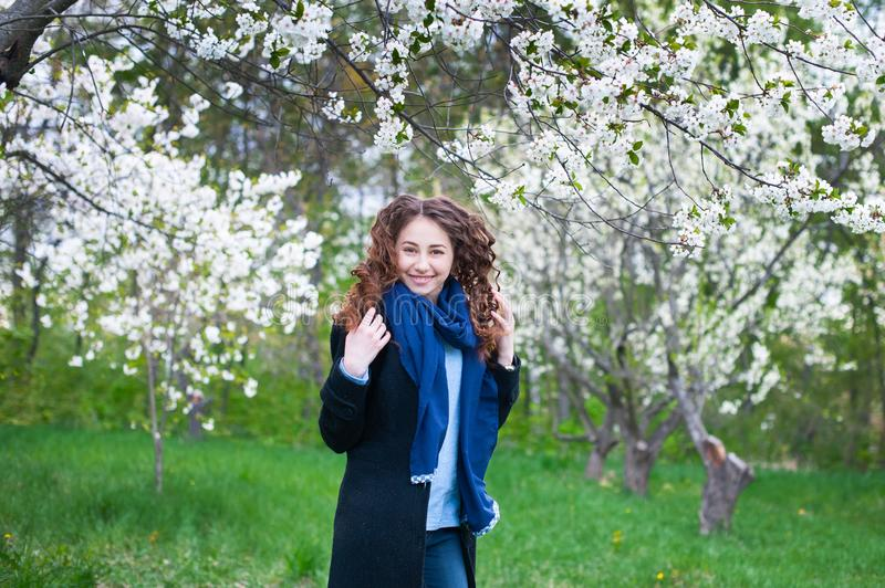 Portrait of a young beautiful fashionable woman in spring blossoming park. Happy girl posing in a blooming garden with white stock photos