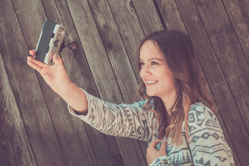 Female taking selfie with retro camera royalty free stock images