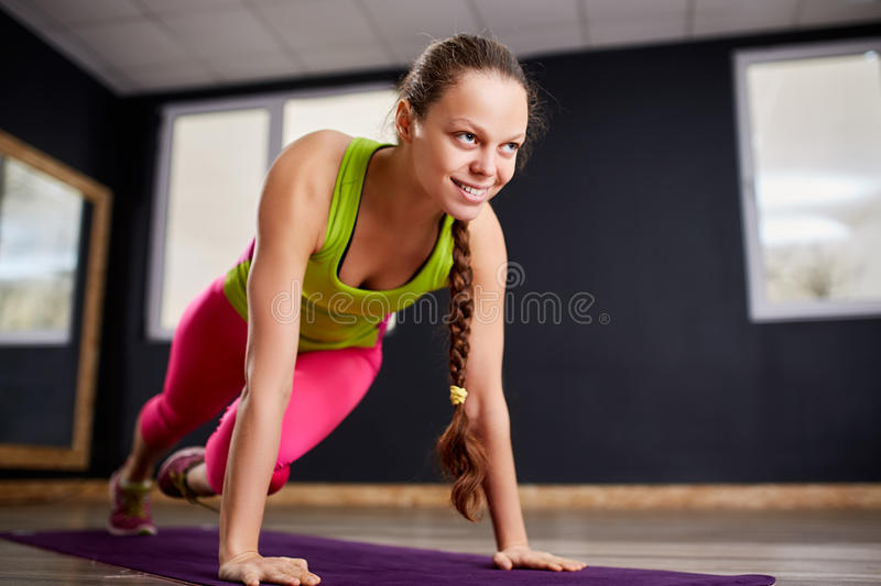 Portrait of the young beautiful fitness woman doing plank position indoors at the gym on the violet yoga mat. stock photo