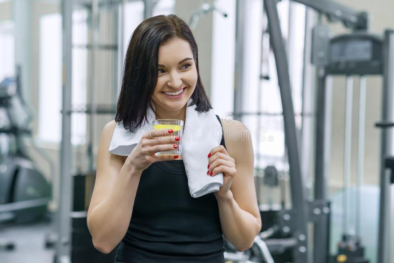 Portrait of young beautiful fitness woman in sportswear with towel, with glass of water and lemon, after fitness classes drinking stock photo