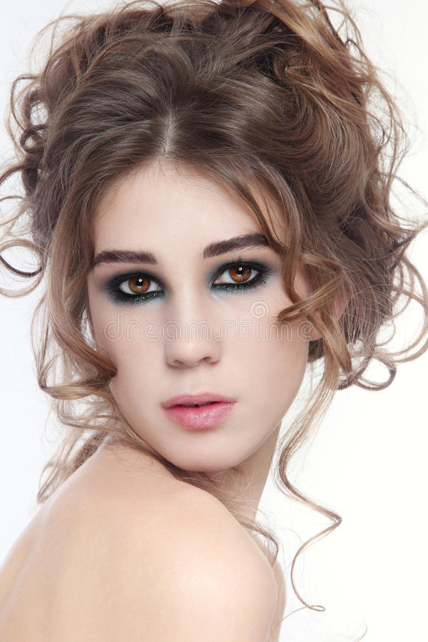 Curly hair. Portrait of young beautiful fresh girl with fancy make-up and hairdo stock images