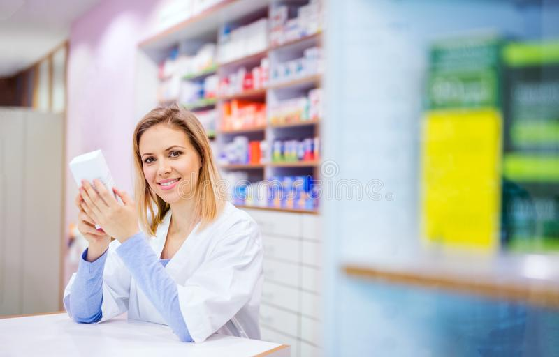 Portrait of a young friendly female pharmacist. stock photo