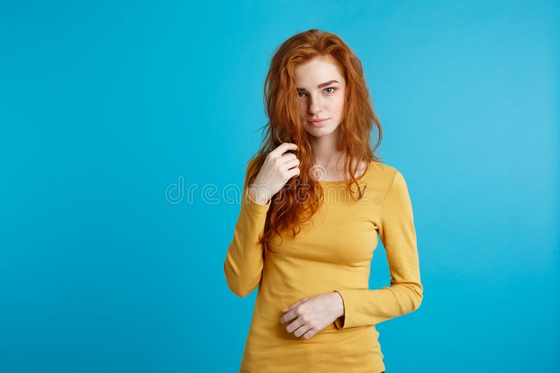 Portrait of young beautiful ginger woman confident looking at camera. Isolated on pastel blue background. Copy space. royalty free stock images