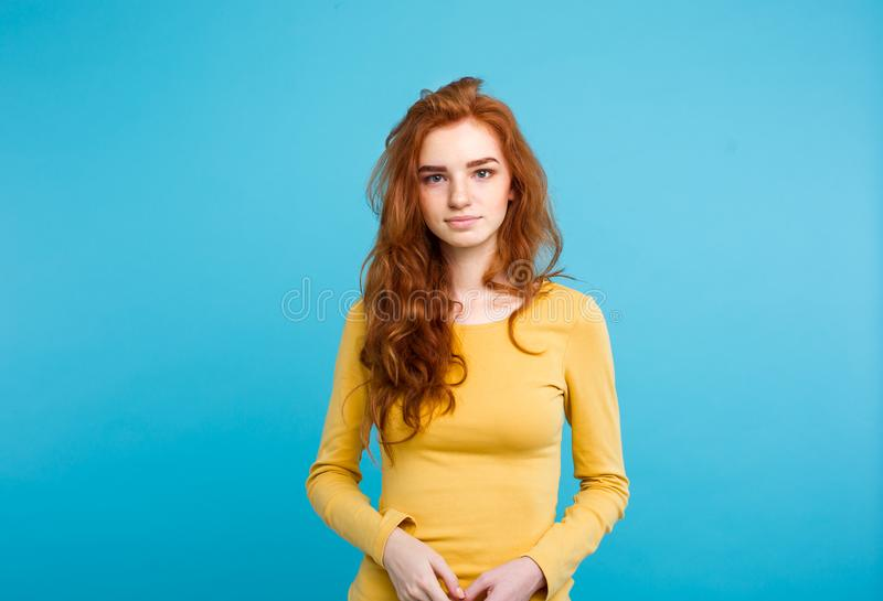 Portrait of young beautiful ginger woman with tender serious face crossing arms looking at camera. Isolated on pastel royalty free stock photos