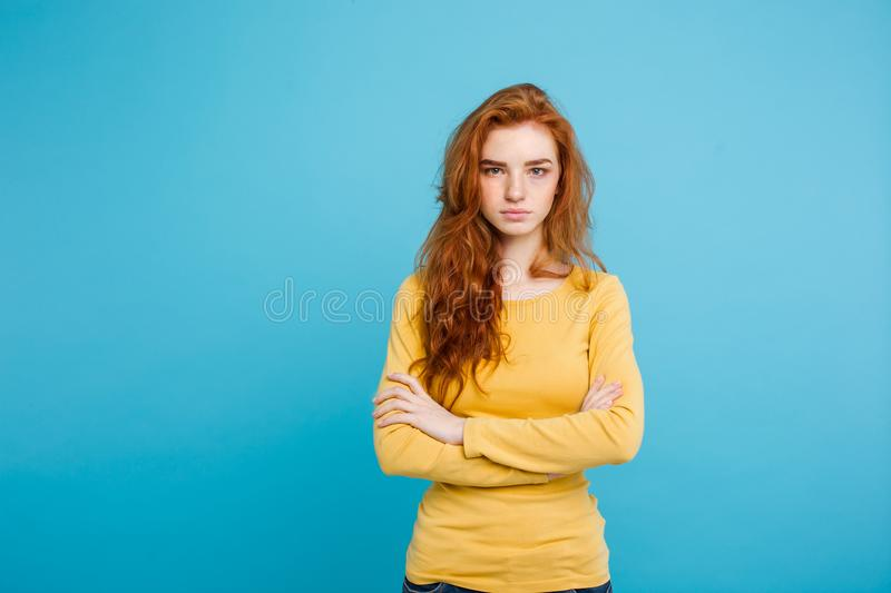 Portrait of young beautiful ginger woman with tender serious face crossing arms looking at camera. Isolated on pastel royalty free stock photo